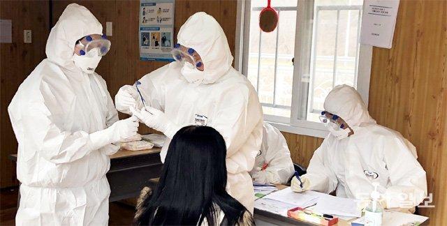 27일 경북 청도군 화양읍 치매안심센터 선별진료소에서 간호사 박은승 씨(왼쪽)가 신종 코로나바이러스 감염증 검사를 하고 있다. 청도=명민준 기자 mmj86@donga.com
