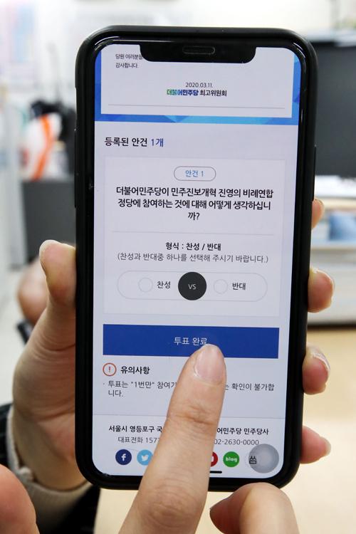 당신의 선택은 더불어민주당 당원이 12일 서울 여의도 국회에서 민주당의 비례연합정당 참여 여부를 결정하는 권리당원 찬반 투표를 하고 있다. 허정호 선임기자