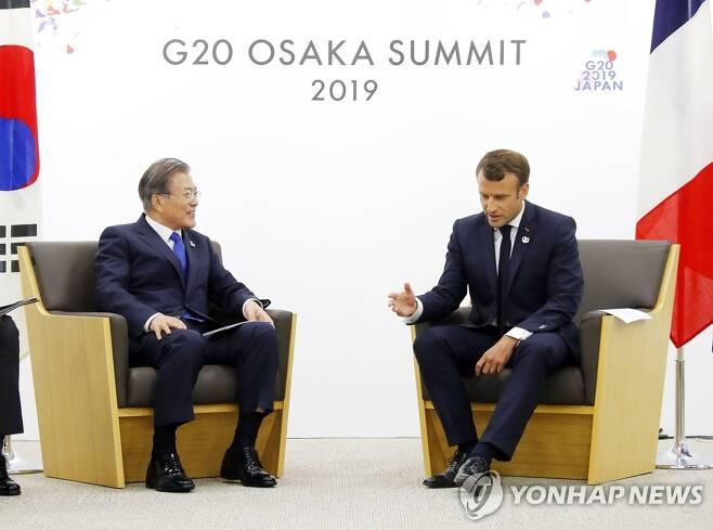문재인 대통령과 에마뉘엘 마크롱 프랑스 대통령이 2019년 6월 28일 오후 G20 정상회담장인 인텍스 오사카 내 양자회담장에서 열린 한-프랑스 정상회담에서 대화하고 있다.[연합뉴스 자료사진]