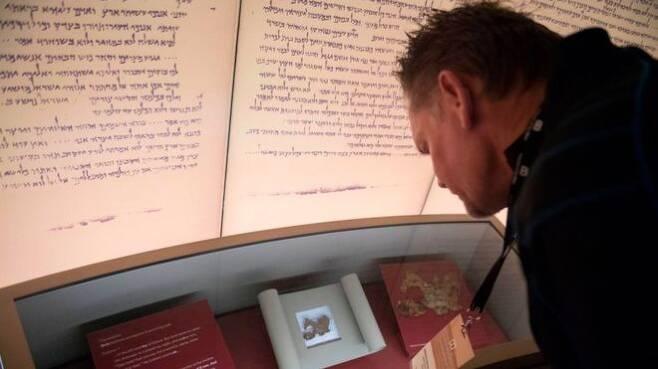 미국 워싱턴 DC에 있는 성경박물관에서 사해 문서 16조각을 구입해 첫 선을 보이기 전 언론 공개 도중 한 참가자가 관련 유물을 유심히 살펴보고 있다.AFP 자료사진