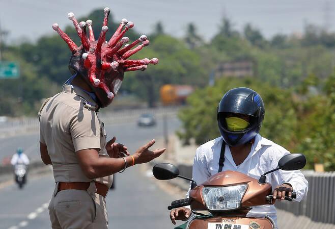 인도 정부가 코로나19 확산을 막기 위해 3주간 '국가 봉쇄령'을 내린 뒤, 28일 첸나이에서 한 경찰이 코로나19 모습을 본 따 만든 헬멧을 쓴 채 오토바이 운전자에게 집으로 돌아가라고 얘기하고 있다. 첸나이/로이터 연합뉴스