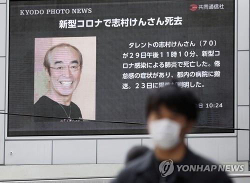 (오사카 로이터=연합뉴스) 일본의 '국민 개그맨' 시무라 겐이 코로나19로 사망했다는 소식을 전하는 대형 스크린 앞을 30일 마스크 쓴 남성이 걸어가고 있다. ucham1789@yna.co.kr