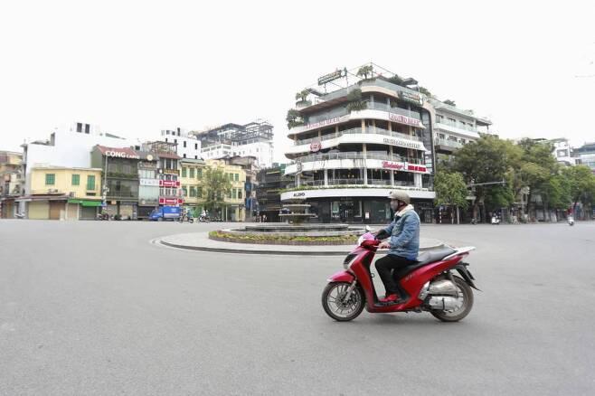 [하노이=AP/뉴시스]1일(현지시간) 베트남 하노이에서 오토바이를 탄 한 남성이 텅 빈 거리를 지나고 있다. 베트남은 신종 코로나바이러스 감염증 확산 예방을 위해 1일부터 보름간 사회적 거리 두기를 강화하고 대중교통 운행을 중단했으며 학교, 병원, 공공장소 등에서 2명 이상 모이지 못하도록 했다. 당국은 격리 규정을 위반하면 최고 징역 5년에 처하는 등 강력히 처벌하기로 했다고 밝혔다. 2020.04.01.