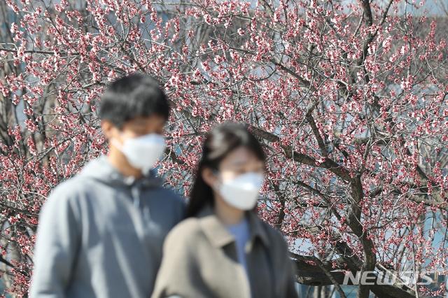 [서울=뉴시스] 이윤청 기자 = 나들이 나온 시민들이 22일 서울 여의도 한강공원에서 마스크를 쓴 채 걷고 있다. 2020.03.22. radiohead@newsis.com