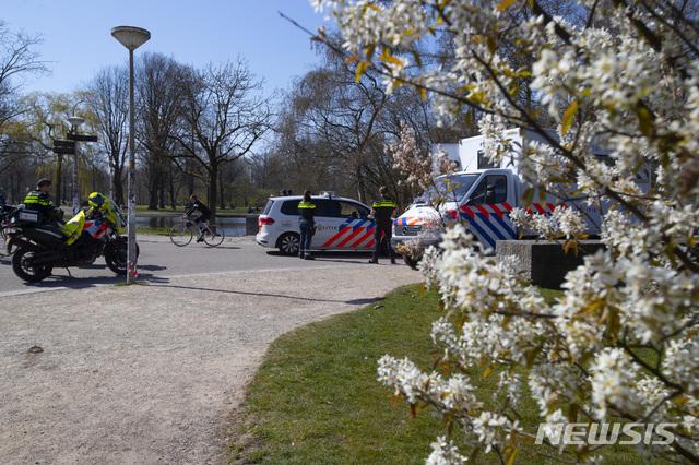 [암스테르담=AP/뉴시스] 네덜란드 경찰이 화창한 주일인 5일 꽃핀 공원에서 상춘객 저지를 위한 순찰을 하고 있다 2020. 4. 5.