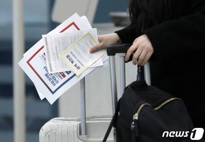 독일 프랑크푸르트에서 온 입국자가 28일 인천국제공항에서 검역확인증을 들고 별도 교통편을 이용하기 위해 이동하고 있다.  2020.3.28/뉴스1 © News1 안은나 기자