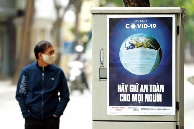 베트남 하노이에 설치된 코로나19 위험을 알리는 표지판 옆을 한 시민이 걷고 있다. ⓒEPA 연합