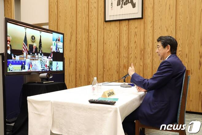아베 신조 일본 총리(오른쪽)가 16일 오후 관저에서 도널드 트럼프 미국 대통령 등 주요 7개국(G7) 정상들과 화상회의를 하고 있다. © AFP=뉴스1
