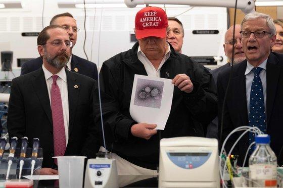 도널드 트럼프 미국 대통령이 지난달 6일 조지아주 애틀랜터 질병통제센터(CDC) 본부를 방문해 신종 코로나바이러스 샘플 사진을 보고 있다. 왼쪽은 알렉스 에이자 보건장관, 왼쪽 뒤가 로버트 레드필드 CDC 소장이다. 당시 이미 CDC가 생산한 진단키트가 불량으로 판명돼 FDA가 민간 기업에 제조를 맡길 것을 권고한 상황이었다.[AFP=연합뉴스]