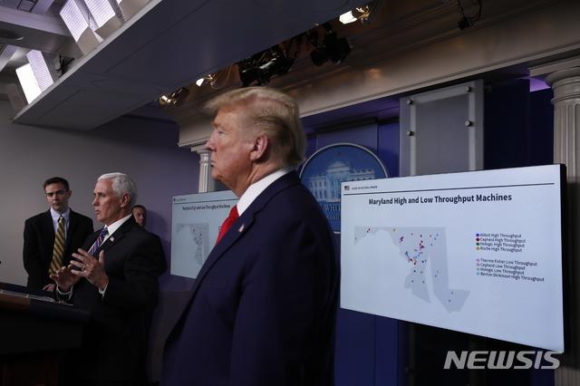 [워싱턴=AP/뉴시스] 20일(현지시간) 미국 워싱턴 백악관에서 열린 신종 코로나바이러스 감염증(코로나19) 태스크포스 브리핑에서 도널드 트럼프 미국 대통령이 마이크 펜스 부통령의 발언을 듣고 있다. 이날 펜스 부통령은 메릴랜드 주의 코로나19 검사시설을 지도로 표시한 슬라이드를 준비해 나와 한국에서 진단키트를 확보한 래리 호건 메릴랜드 주지사를 질책했다. 2020.4.21.