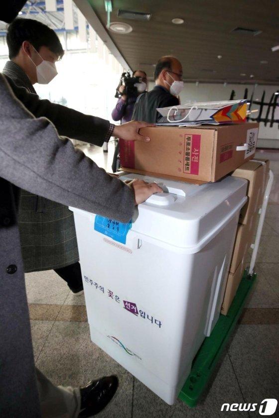 제21대 국회의원선거 사전투표가 종료된 11일 오후 서울 용산구 서울역 대합실에 마련된 남영동 사전투표소에서 투표관리관이 관·내외 선거인 투표 봉투가 담긴 상자와 투표함을 용산구 선관위로 옮기기 위해 이동하고 있다.2020.4.11/사진 = 뉴스1