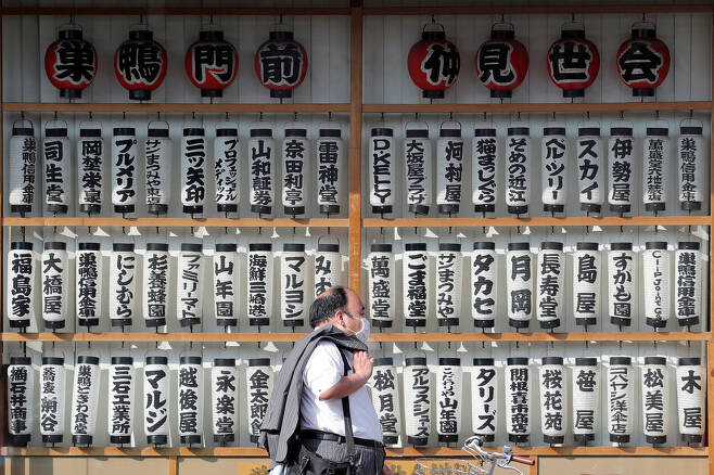 일본 도쿄에서 마스크를 쓴 남성이 상점가를 지나가고 있다. 도쿄/로이터 연합뉴스