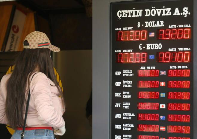지난 7일(현지시간) 터키의 이스탄불에 있는 한 환전소를 찾은 여성이 전광 시세판을 살펴보고 있다. 이날 달러화에 대한 터키 리라화의 가치는 신종 코로나바이러스 감염증(코로나19) 사태로 인한 경제 충격으로 사상 최저를 기록했다. [연합]