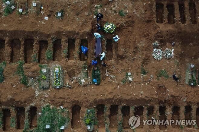 22일(현지시간) 브라질 상파울루의 한 묘지에 코로나19 사망자가 매장되고 있다. [AFP=연합뉴스]