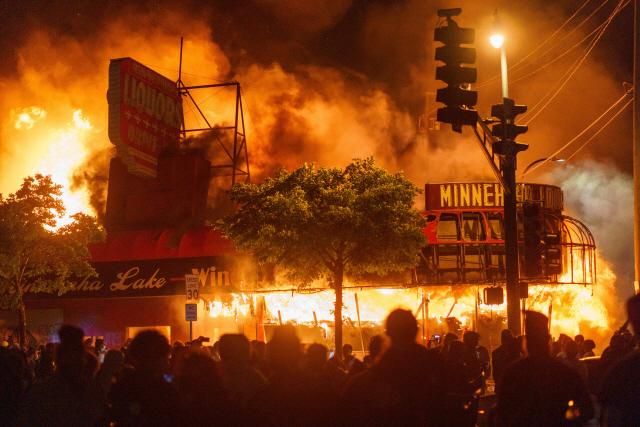 사흘 전 흑인 남성이 경찰에게 목이 짓눌려 사망한 사건에 분개한 미국 시민들이 28일(현지시간) 미네소타주 미니애폴리스 3관할 경찰서 근처의 불타는 주류 판매점 앞에 모여 격렬한 시위를 벌이고 있다.   /AFP연합뉴스