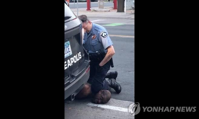 무릎으로 흑인 용의자 목누르는 미국 경찰관 (미니애폴리스 AFP=연합뉴스) 25일(현지시간) 미국 미네소타주 미니애폴리스에서 경찰이 무릎으로 한 흑인 남성의 목을 누르고 있다. 위조 수표 신고를 받고 출동한 경찰관이 범인으로 의심되는 흑인을 체포하는 장면으로, 당시 현장을 지나가던 행인이 페이스북에 올린 비디오에서 캡처한 사진. 이 흑인은 경찰의 이러한 행위로 결국 숨졌으며 연방수사국(FBI)은 사망 경위 수사에 착수했다. [재판매 및 DB 금지] ymarshal@yna.co.kr