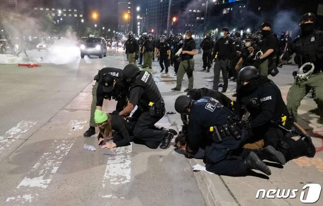 30일(현지시간) 미시간주 디트로이트에서 비무장 흑인 남성 조지 플로이드의 백인 경찰 가혹 행위로 숨진 사건에 항의하는 시위대를 경찰이 강제 체포하고 있다. © AFP=뉴스1 © News1 우동명 기자