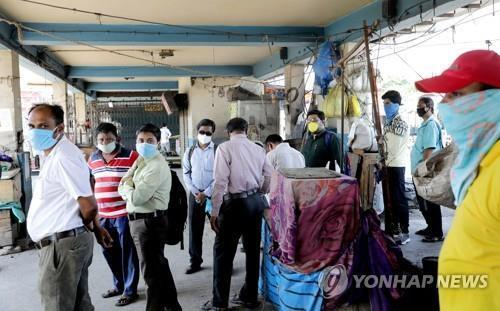 인도 콜카타에서 마스크를 쓰고 통근용 정부 버스를 기다리는 주민. [EPA=연합뉴스]