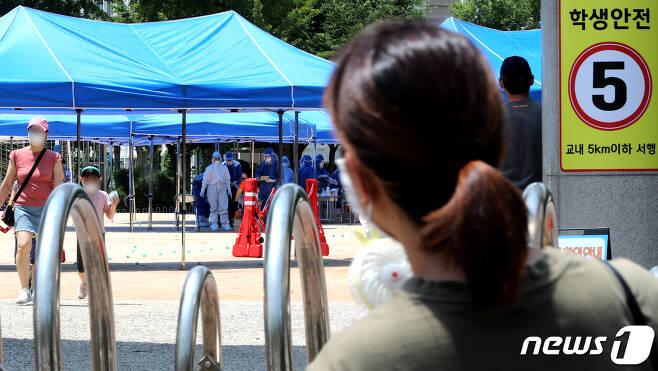 14일 오후 인천 계양구 효성초등학교에 마련된 선별진료소에서 검사를 마친 학생들이 부모의 손을 잡으며 학교를 빠져 나오고 있다. 방역당국은 해당 학교를 다니고 있는 A군(10)이 코로나19 양성판정을 받았다고 밝혔다. 이 학교는 26일까지 원격수업으로 전환됐다.2020.6.14/뉴스1 © News1 정진욱 기자