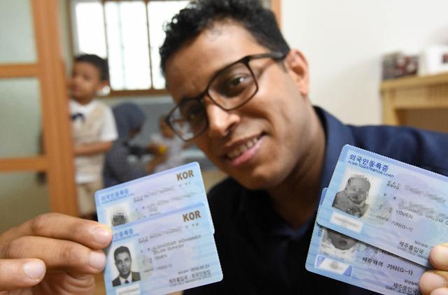 제주 서귀포시 남원군에 거주 중인 모하메드씨가 6월 12일 기자에게 온 가족의 외국인등록증을 보여주고 있다. 그의 뒤로 아들 함자와 아내, 딸의 모습이 보인다. 서귀포=서재훈 기자