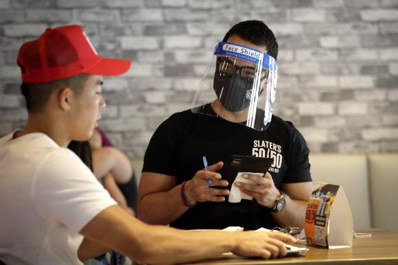 미국 캘리포니아의 한 식당에서 1일 얼굴 보호 마스크를 착용한 점원이 음식 주문을 받고 있다. 연합뉴스
