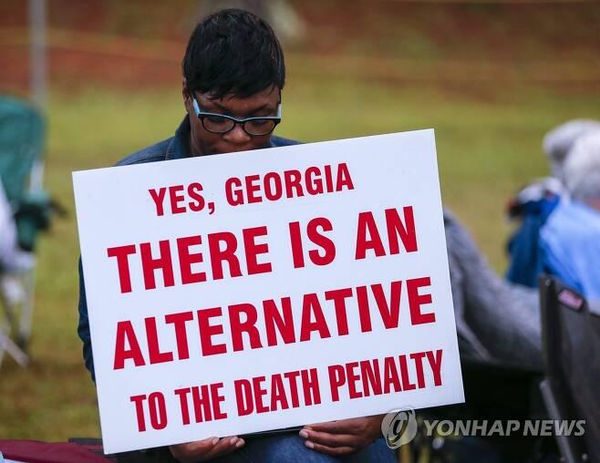 """지난 2015년 9월 29일 미국 조지아주에서 열린 사형제 반대 집회에 참가한 한 시민이 """"사형제의 대안이 있다""""는 팻말을 들고 있다. [EPA=연합뉴스 자료사진]"""
