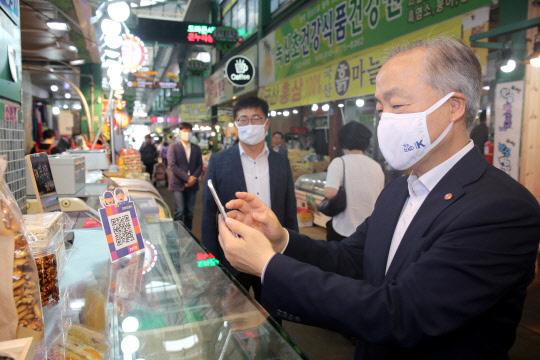 조봉환(오른쪽) 소상공인시장진흥공단 이사장이 지난달 30일 대전 도마큰시장에서 상품을 구매한 후 '모바일 온누리상품권'으로 결제하고 있다.     소진공 제공