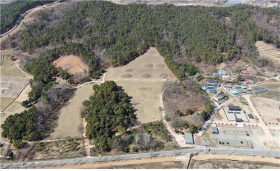 공중에서 본 부여 능산리 고분군 전경. 중간에 일곱개의 무덤 자리가 보이는 곳이 능산리 중앙고분군이며, 왼쪽 상단에 숲으로 둘러싸인 네모진 구역이 지난 2016년 4기의 무덤이 발굴된 서고분군이다.