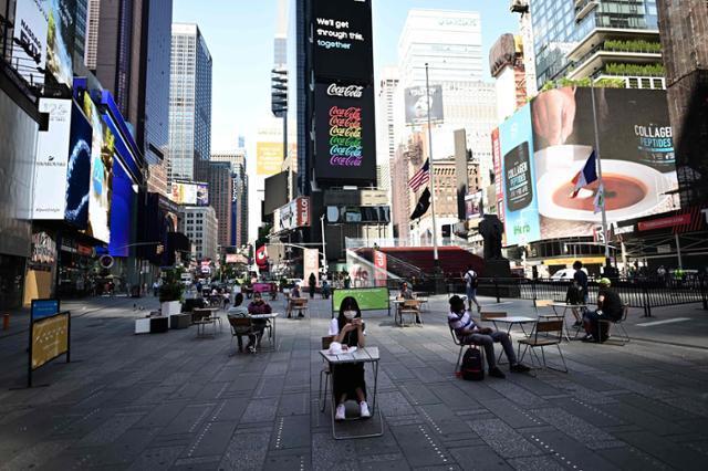 미국에서 신종 코로나바이러스 감염증(코로나19)으로 가장 큰 타격을 입었던 뉴욕시가 2단계 경제 재개 조치에 들어간 지난달 22일(현지시간) 맨해튼 중심가 타임스퀘어에서 사람들이 '사회적 거리두기'를 지키며 탁자에 앉아 있다. 뉴욕=AFP 연합뉴스