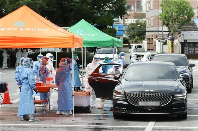 16일 오전 광주 동구청 드라이브 스루(Drive Through) 선별진료소에서 구청 보건소 직원들이 차량에 탄 시민과 아이들의 검체를 채취하고 있다. 2020.7.16 광주 동구 제공
