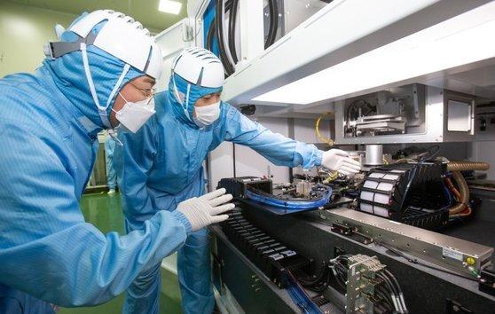 삼성전자 직원(왼쪽)과 이오테크닉스 직원이 양사가 공동 개발한 반도체 레이저 설비를 함께 살펴보는 모습. [사진 삼성전자]