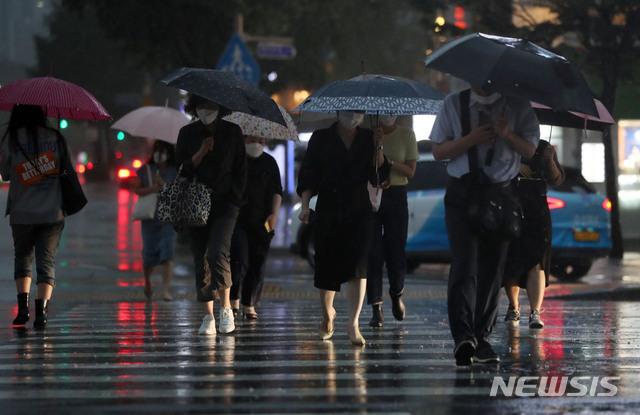[서울=뉴시스] 박미소 기자 = 서울에 호우주의보가 발효된 지난 23일 오후 서울 종로구 광화문네거리에서 시민들이 우산을 쓰고 걸어가고 있다. 2020.07.23.  misocamera@newsis.com