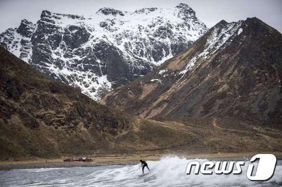 스웨덴의 관광객이 지난 4월17일(현지시간) 북극권에 속하는 로포텐 제도의 운스타드 해변에서 서핑을 즐기고 있다. © News1 이기창