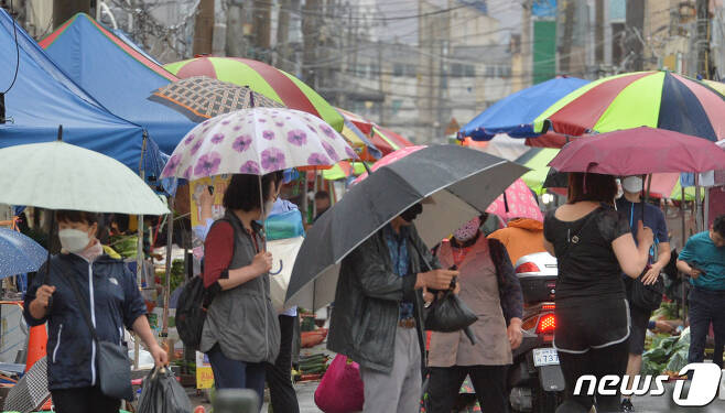 전국에 장맛비가 내리고 있는 28일 오전 경북 포항시 북구 죽도시장에서 시민들이 우산을 쓰고 장을 보고 있다. 2020.7.28/뉴스1 © News1 최창호 기자