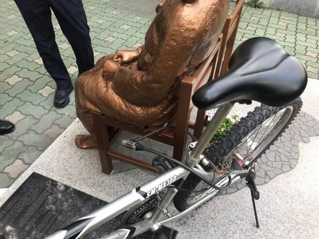 자전거 묶인 부산 소녀상 (서울=연합뉴스) 8일 부산 동부경찰서에 따르면 이날 오후 자전거 한 대가 부산 동구 일본영사관 앞 평화의 소녀상에 철근 자물쇠로 묶여 있는 것을 인근에서 근무 중이던 경찰이 발견했다. 2020.7.8 [소녀상을 지키는 부산시민행동 제공. 재판매 및 DB 금지] photo@yna.co.kr
