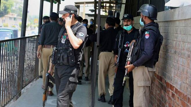 파키스탄 북부 페샤와르 법원 앞 경찰들 신성모독 혐의로 재판 중 총격 피살 사건이 발생한 후 경찰들이 법원 문앞을 경계하고 있다. [AP뉴스 재판매 및 DB금지]