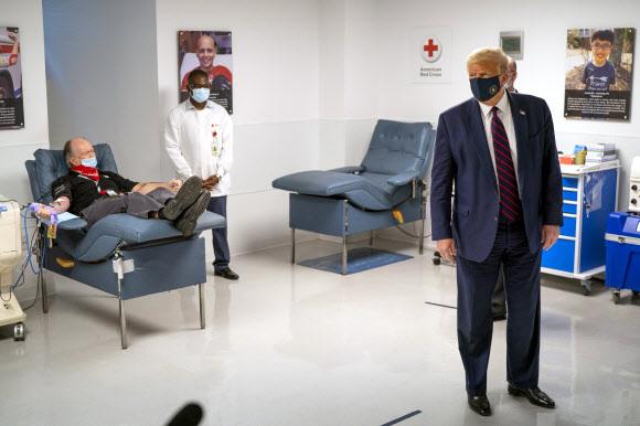 도널드 트럼프 미국 대통령이 30일(현지시간) 워싱턴의 미국 적십자사 본부를 찾아 코로나19 퇴치를 위해 혈장을 기증한 환자를 바라보고 있다.워싱턴 풀 기자단 AP 연합뉴스