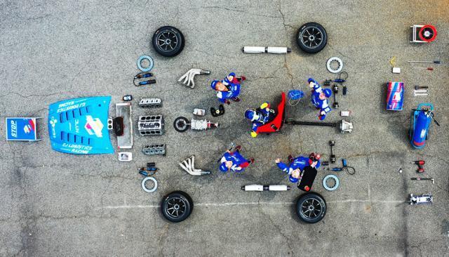 CJ로지스틱스 미캐닉이 17일 용인 팀 캠프에서 경주용 자동차 부품을 펼쳐 놓은 가운데 드론을 향해 포즈를 취하고 있다. 용인=홍인기 기자
