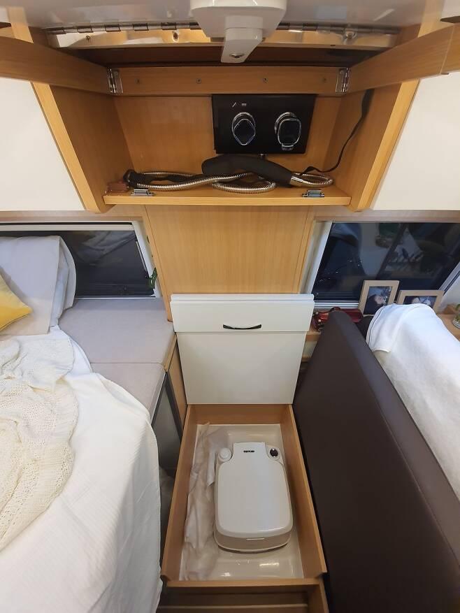 리빙룸과 침대 사이에 위치한 휴대용 화장실겸 샤워부스, 수전은 상부 수납장에 위치하고 커튼을 위한 프레임이 마련되었다
