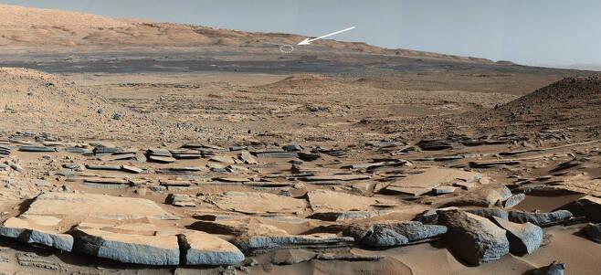 지난 2014년 3월 24일 큐리오시티가 촬영한 화성 표면의 전경이다. 저멀리 화살표가 가르키는 원이 2020년 7월 30일 기준 큐리오시티가 현재 있는 위치로 대략 5㎞ 정도 떨어져있다.