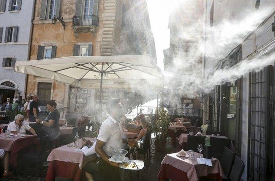지난달 31일 폭염에 시달리는 이탈리아의 한 야외 카페에서 수증기 스프레이를 분사해 더위를 식히는 모습 [AP=연합뉴스]
