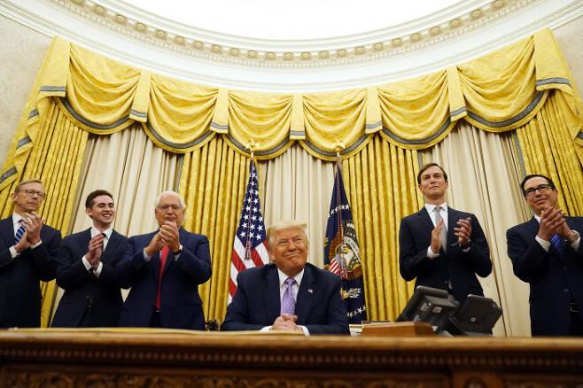 도널드 트럼프 미국 대통령(가운데)이 13일(현지시간) 백악관 집무실에서 기자들에게 이스라엘과 아랍에미리트연합(UAE)이 외교관계 정상화에 합의했다고 발표하자 옆에 있던 참모진이 박수를 치고 있다. 워싱턴   AP연합뉴스