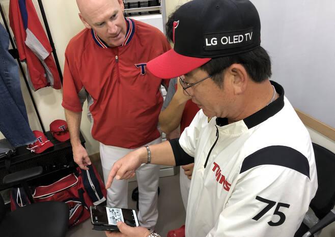 12일 잠실 경기를 앞두고 류중일 LG 감독이 1985년 한미대학선발 교류전 사진을 당시 미국대학팀 일원이었던 맷 윌리엄스 KIA 감독에게 보여주고 있다. 사진제공=KIA 타이거즈