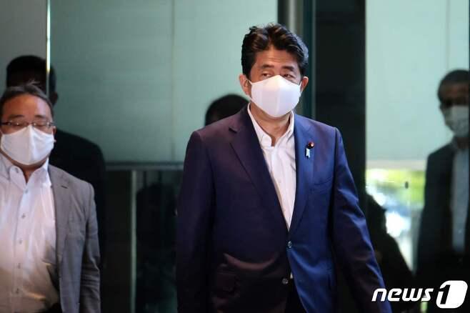 마스크를 착용한 아베 신조 일본 총리(가운데)가 지난 19일 오후 관저로 출근하고 있다. © AFP=뉴스1