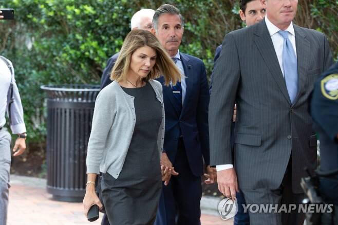 손을 잡고 걸어가는 법정으로 향하는 로리 러프린 부부 [UPI=연합뉴스 자료사진]