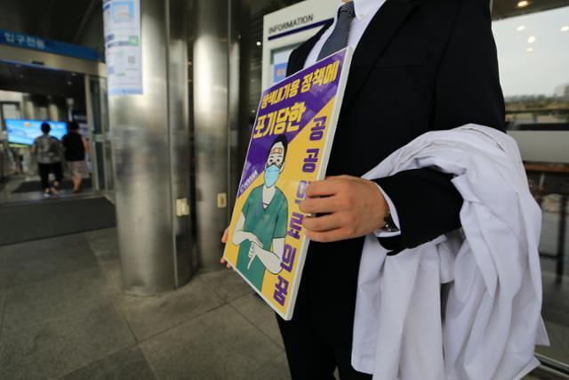 의과대학 정원 확대 등 정부의 의료정책에 반대하는 인턴, 레지던트 등 전공의들이 순차적 파업에 돌입한 21일 서울 종로구 서울대병원에서 의과대학 학생이 1인 릴레이 시위를 하고 있다. 뉴스1