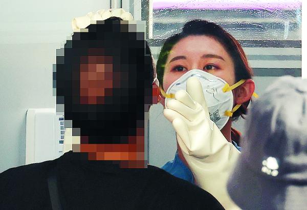 의료진이 25일 서울 중구 국립중앙의료원에 마련된 코로나19 외부 검체 채취실에서 투명한 의료용 분리벽을 사이에 두고 내원객의 검체를 채취하고 있다.    연합뉴스