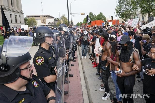 [커노샤=AP/뉴시스]24일(현지시간) 미 위스콘신주 커노샤에 있는 커노샤 카운티 법원 앞에서 시위대가 팔짱을 끼고 경찰과 대치하고 있다. 앞서 23일 차량에 탑승하려던 비무장 흑인 제이컵 블레이크라는 남성이 자신의 세 자녀가 보는 앞에서 백인 경찰의 총에 7발이나 맞는 사건이 일어나 조지 플로이드 사망 사건을 상기시키며 분노의 시위를 촉발했다. 토니 에버스 위스콘신 주지사는 폭력 시위를 막기 위해 100여 명의 주 방위군을 소집했다. 2020.08.25.