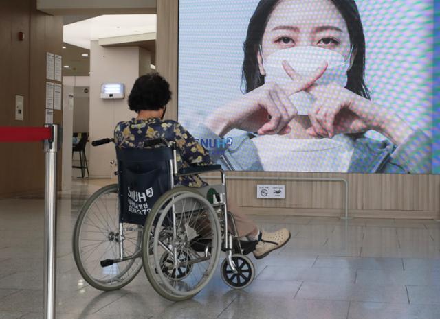 대한의사협회가 사흘간의 2차 전국의사 총파업에 돌입한 26일 서울 종로구 서울대병원에서 휠체어를 탄 환자가 병원 전광판 앞에서 생각에 잠겨 있다. 뉴스1