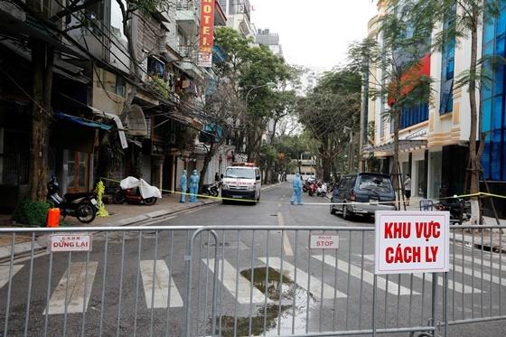 의료진이 하노이 거리에서 코로나19 감염자 집 근처 구급차 앞에 서있다/사진=로이터